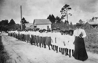 Historic photo of Mary McLeod Bethune at the front of a line of students, early 1900s.