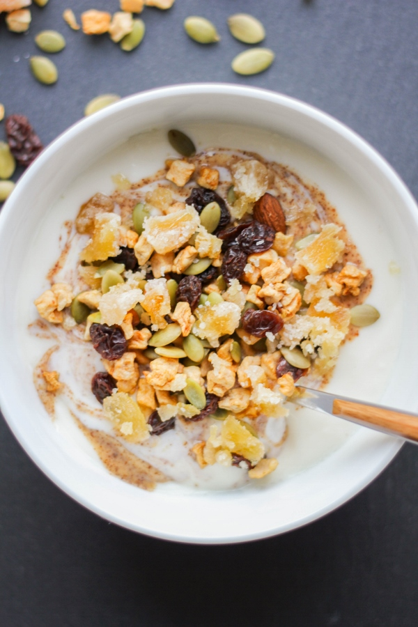 This protein packed delicious yogurt bowl starts with creamy vanilla grassfed yogurt and is topped with almond butter, harvest trail mix, and bites of sweet and spicy crystallized ginger. It's the best way to start your day!