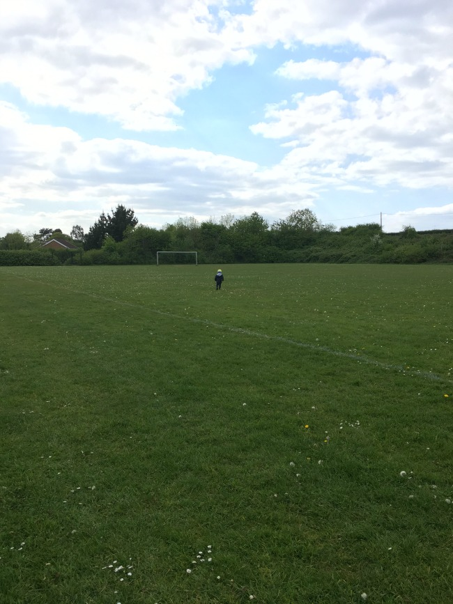 toddler-in-playing-field-with-goal-posts-in-the-background