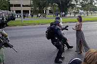 Black nurse standing up to police officers in gear and armor