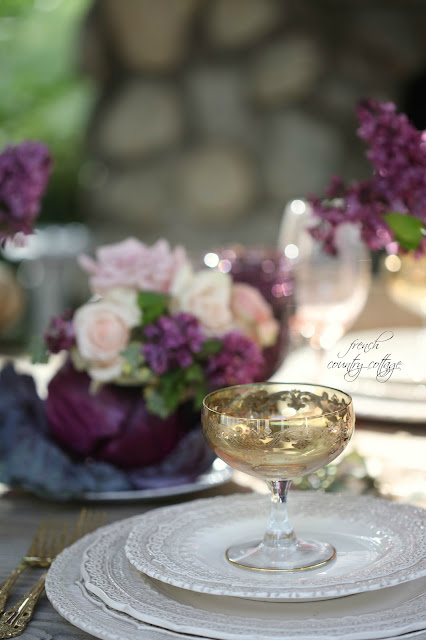 Purple flowers and gold glasses on table outdoors