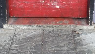 Close-up of the step: the bottom of the red wooden door which has scuff marks on its lower third and is set in a black door frame. The red-painted, concrete floor of the toilet area protrudes from under the door, creating a step which is approximately 5 cm or 2 inches tall. The path in front of the door is made of grey slate pavers.