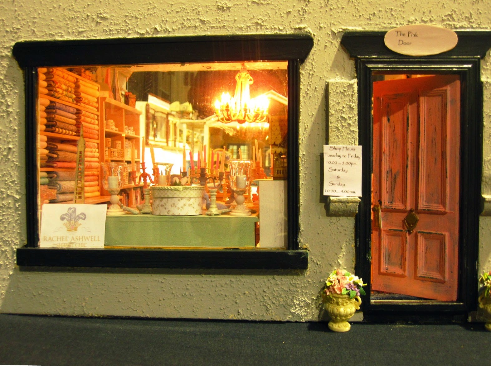 Close up of a modern miniature shop, showing a display window showing shabby chic items and a pink front door.
