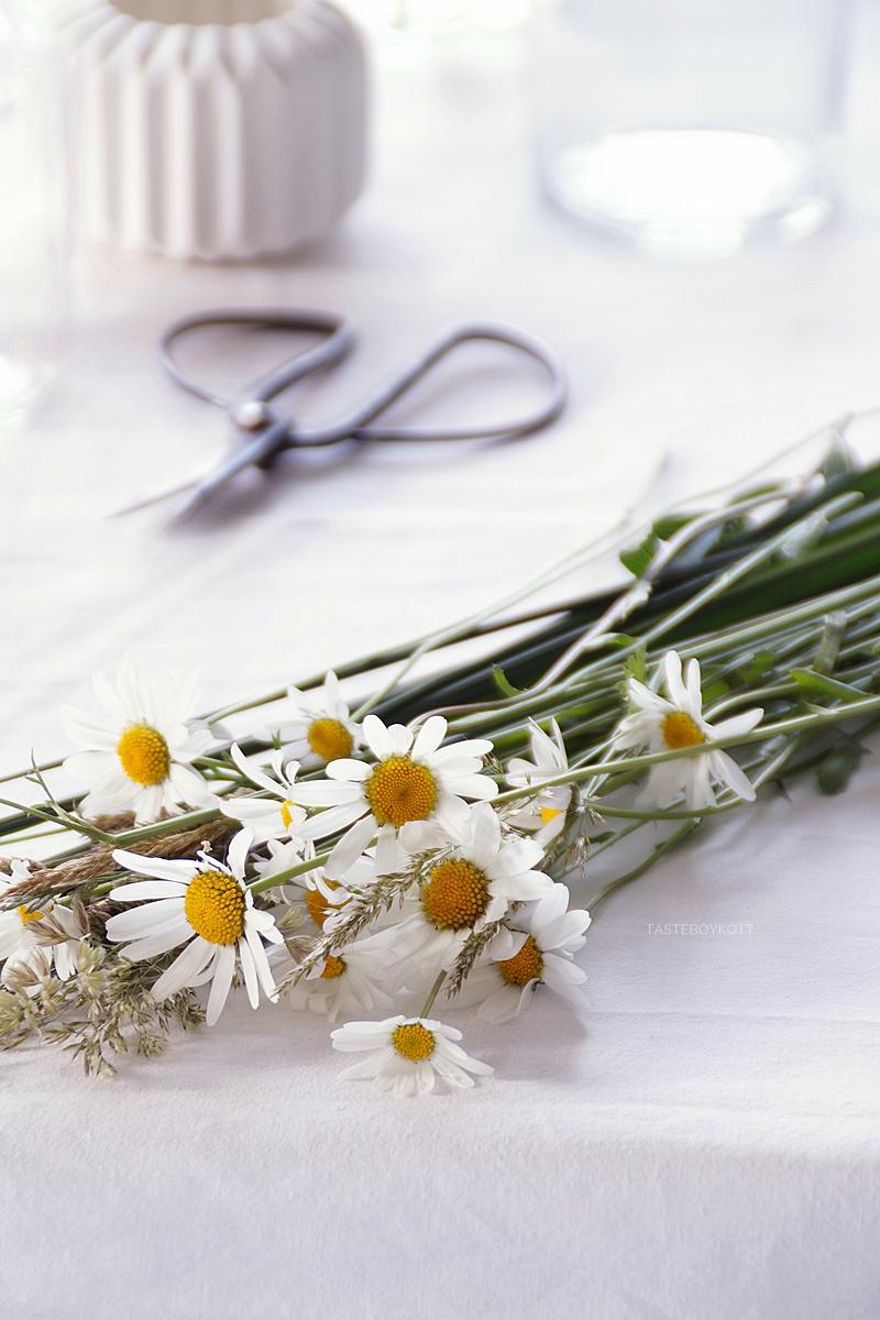 Tisch sommerlich dekorieren mit Margeriten, Giersch, Gräsern und Zweigen in Glasflaschen und einer weißen Tischdecke | Tasteboykott