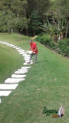 Bizzarri trabalhando, fazendo um caminho de pedra no jardim, sendo caminho com cacão de Goiás com junta de grama em casa em condomínio na Cantareira. 1 de fevereiro de 2017.