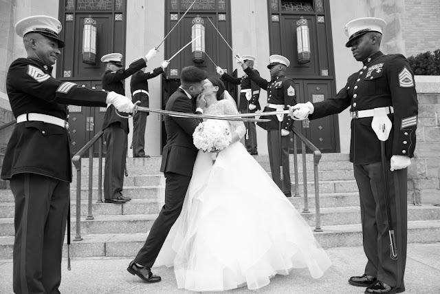 Soldier's swords make an arch for the couple to kiss under in front of the church