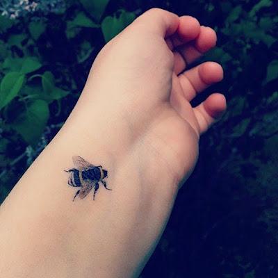 chica con tatuaje de abeja en el antebrazo