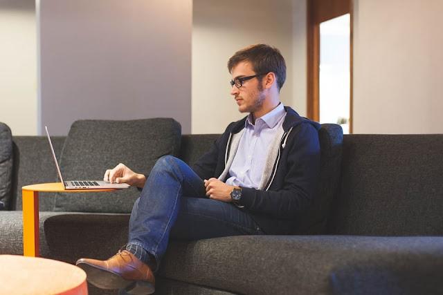 Homem sentado no sofá usando notebook