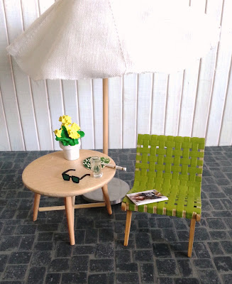 One-twelfth scale modern miniature paved patio with a Jen Rison webbed chair, a side table and patio umbrella. On the side table is a potted plant, a fan, a pair of sun glasses and a glass of water. On the chair is a magazine.