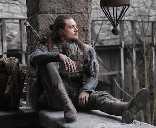 Uhtred de Bebbanburg sentado, apoyando la espalda en una columna. Tiene el pelo largo, viste con ropa de guerrero, y lleva a la espalda su famosa espada con un ámbar en la empuñadura.