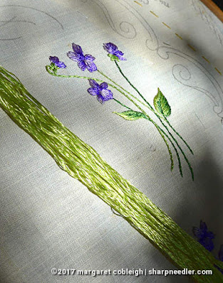 Society Silk Violets: completed embroidered violets with skein of highly reflective antique silk floss