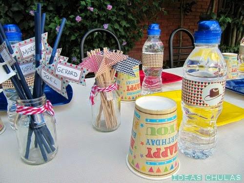 Mesa decorada con toppers, botellas con etiquetas y pajitas con el nombre