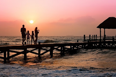 Uma família contemplando o por do sol refletindo sobre o mar