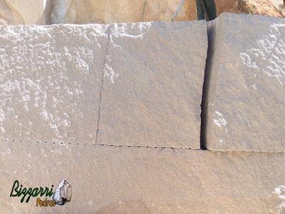 Pedra de granito bruto sendo cortada para execução de pedra paralelepípedo.