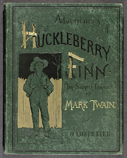 A green book cover for Huckleberry Finn, stamped in gold and black.