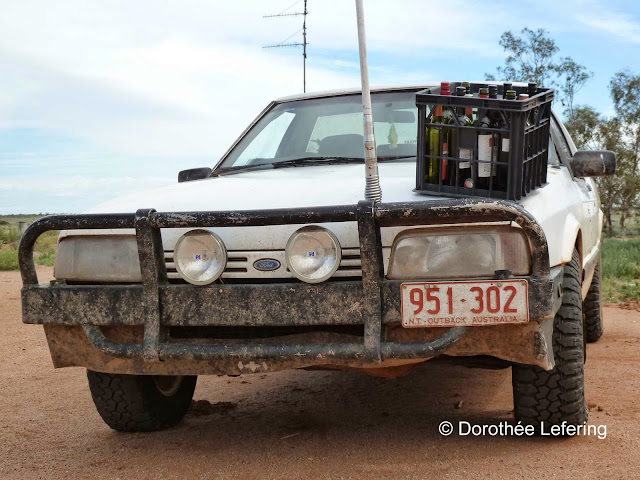 A dirty white vehicle with a crate of wine bottles on the hood parks on a red dusty unpaved road.