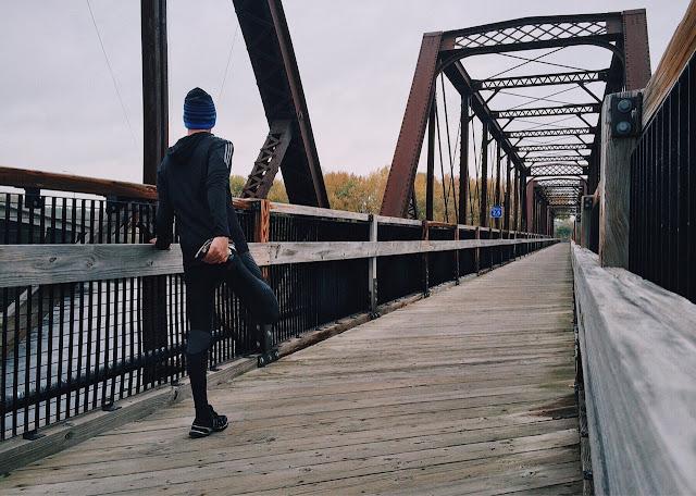 Man on bridge stretching, preparing to run