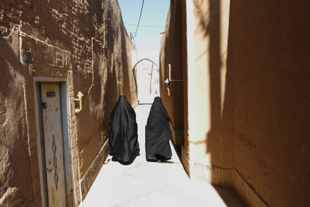 Muslim ladies walking through the narrow alleys of Yazd old town