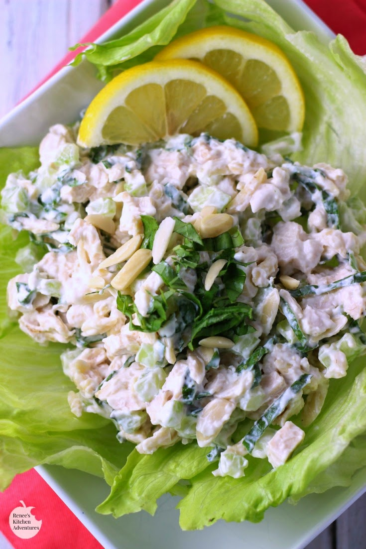 Creamy Lemon and Fresh Basil Chicken Salad by Renee's Kitchen on a lettuce leaf, ready to eat with a few lemon slices as garnish at the top of the plate