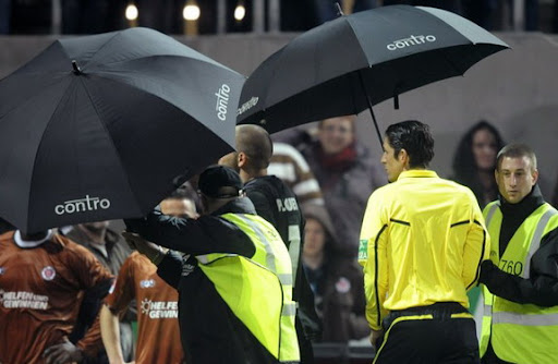 Referee Deniz Aytekin is shielded with umbrellas as he leaves the pitch