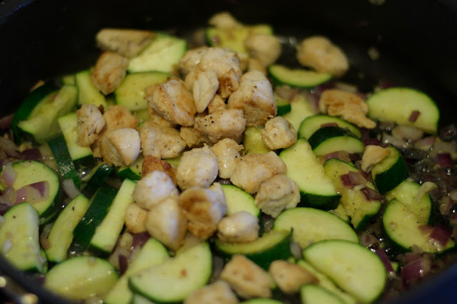 The chicken being returned to the pan with the zucchini, garlic, and onion.