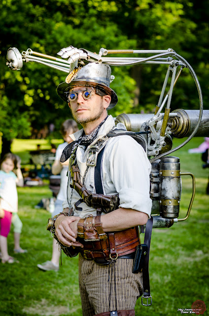 Steampunk man wearing a strange gadget/contraption strapped to his back. Mechanical arm and hand, plus baby doll head