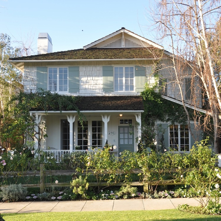 Charming Exterior of California beach cottage with rosebushes in Santa Monica by Giannetti Home