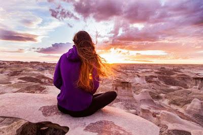 Chica sentada de espaldas mira hacia un paisaje árido y erosionado