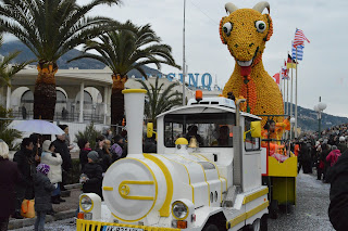 Pic of carnival float - small white train in front with goat out of lemons and oranges behind