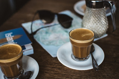 A photo of Canarian coffees with a travel guide book and sunglasses