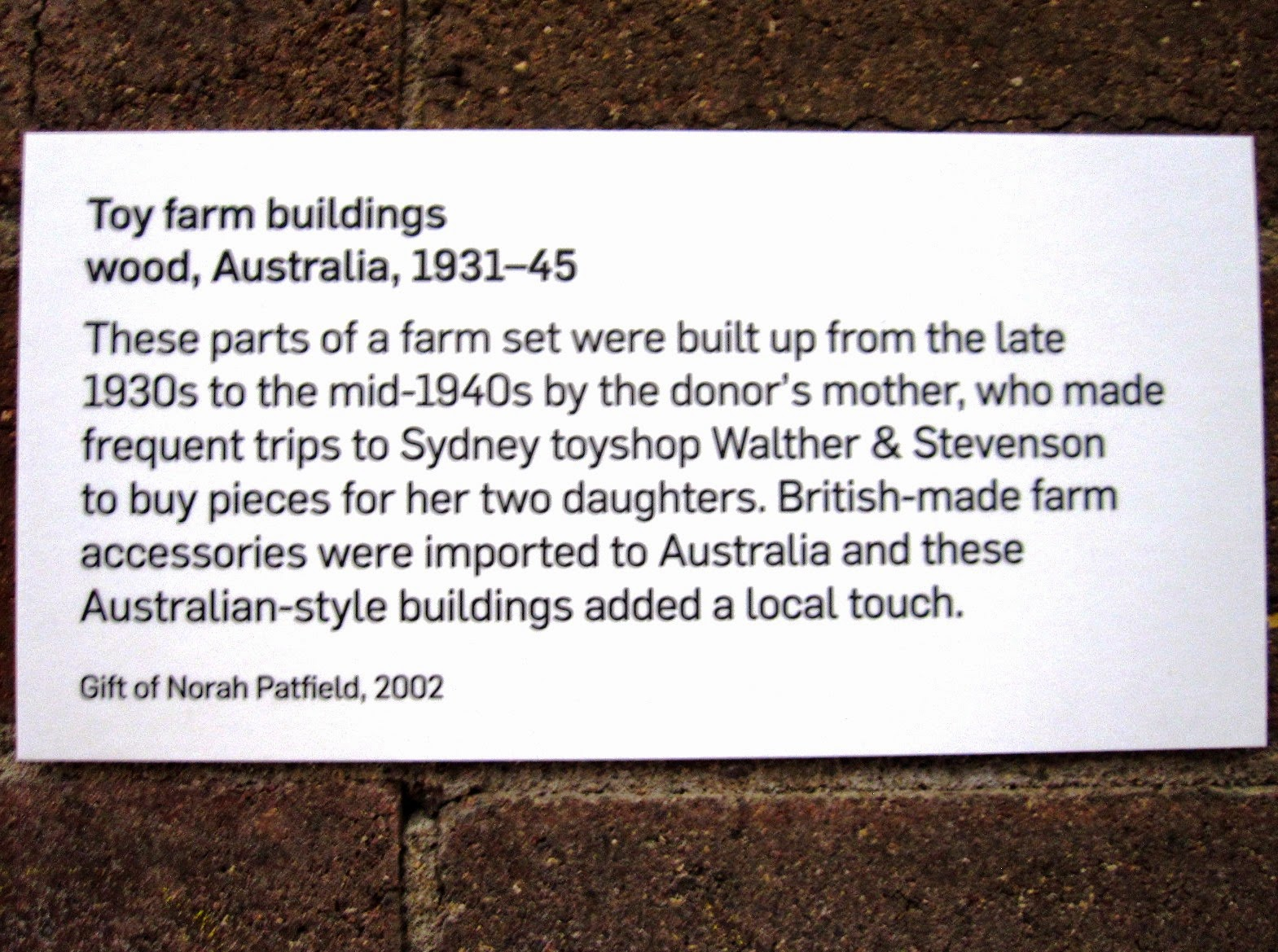 Museum exhibition explanatory sign for a display of vintage toy farm buildings from Sydney shop Walther & Stevenson.
