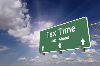 Highway sign that reads tax time, just ahead with three arrows pointing up.