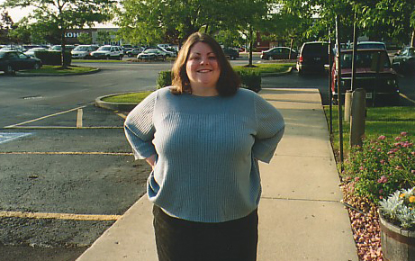 image of me at age 28, standing in a landscaped parking lot, with contacts in and my hair cut into a short bob, wearing a blue sweater and black jeans