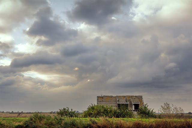 Sickly storm clouds over an old house at Ouse Washes in Cambridgeshire