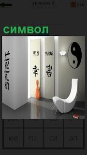 На белых стенах изображение символа и белое кресло, рядом стоят кегли оранжевые