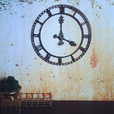 Industrial miniature scene of a large metal clock on a distressed wall behind a desk with various brass items displayed on it.