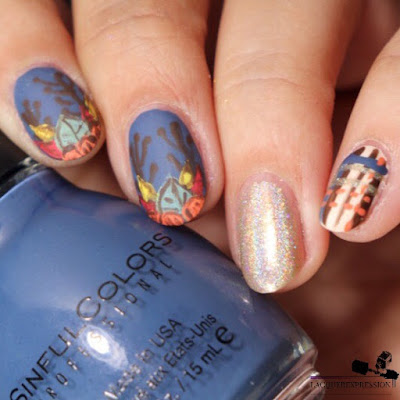 hand painted nail art design with fall leaves and pumpkin over a blue background for Thanksgiving
