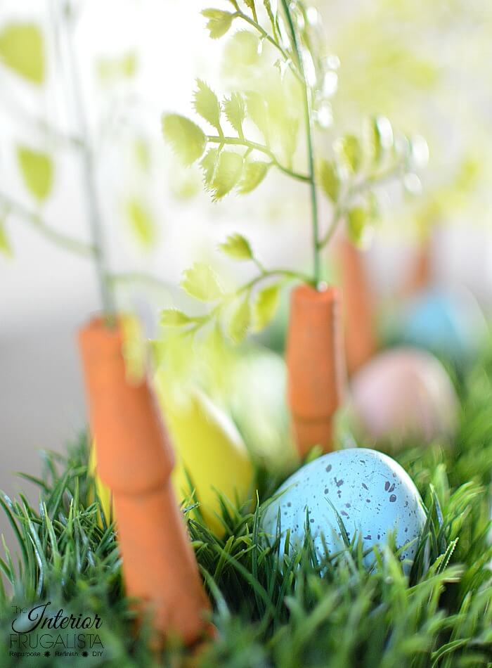 An upcycled Easter centerpiece box with faux wheatgrass, chair spindle carrots, and DIY speckled eggs for a fun budget Easter table decoration idea.