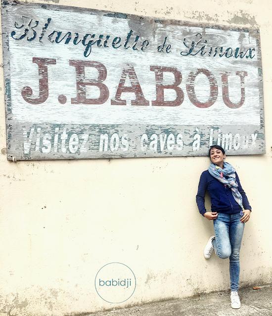 femme devant une ancienne pub sur la façade d'une maison à Axat pour la blanquette de Limoux Babou