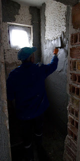 Sally putting the cement on the wall