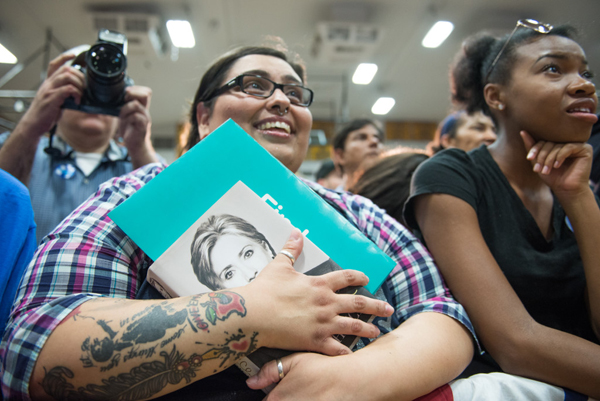 image of a fat, tattooed, white woman at a Hillary rally, clutching one of Hillary's books and looking up at the stage with a look of awe on her face; she is surrounded by a crowd, including an equally enamoured black woman just beside her