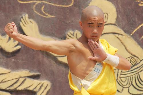 Chinês com aparência de monge do Templo Shaolin, fazendo pose de lutador de kung fu