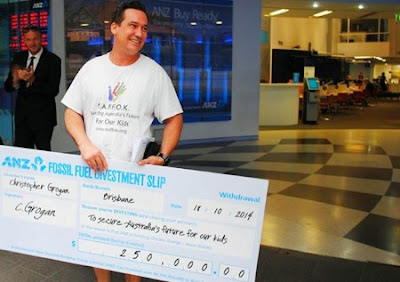 Man with a large novelty cheque to celebrate his divestment from banks investing in fossil fuels
