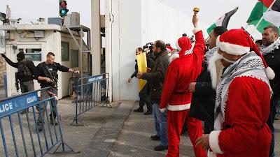 Palestinos, algunos vestidos de Santa Claus, protestan en una sección del llamado muro de separación en la ciudad bíblica de Belén, en la Cisjordania ocupada, 23 de diciembre de 2016.