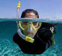 Yüzen bir bayanın ağzındaki şnorkel