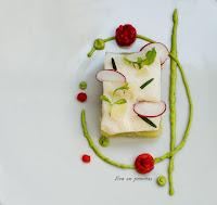 Filete de bacalao al vapor, sobre lamina cuadrada de patata al micro, decorado con un circulo de crema de aguacate y gotas de salsa de piemiento.