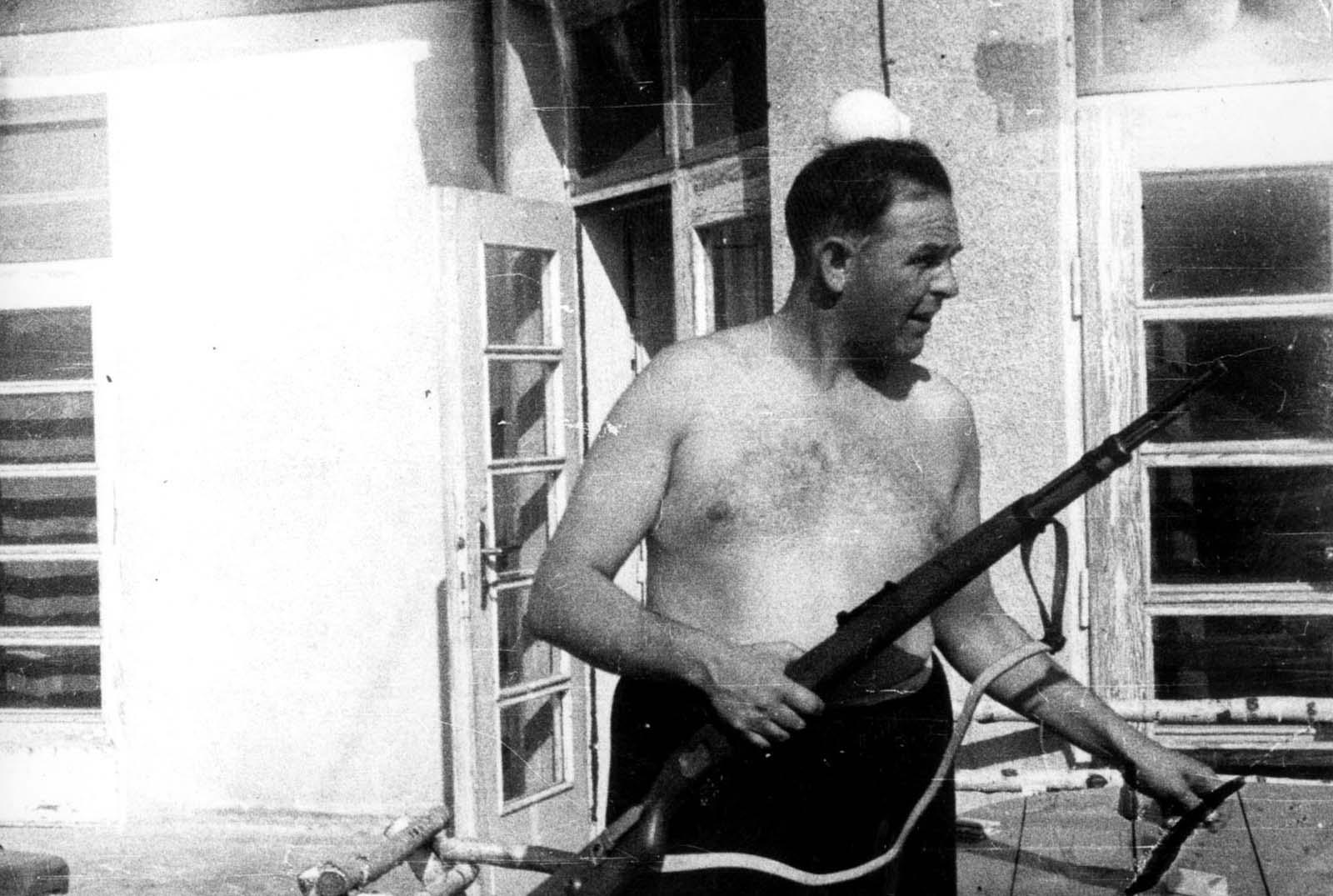 Commandant Amon Leopold Goeth holding a military rifle.