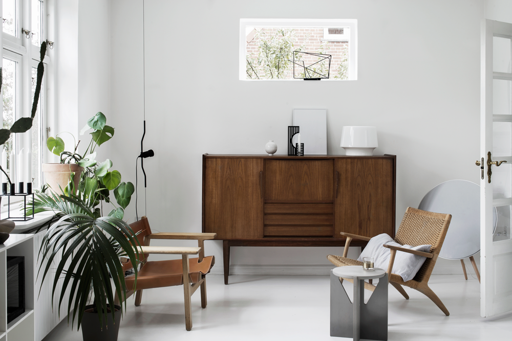 scandianvian interior with houseplants, danish modern furniture and white painted floor