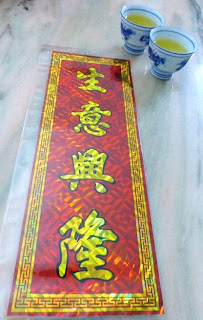 Scroll saying 生意興隆/生意兴隆  (sheng yi xing long), or 'may the  business thrive greatly'