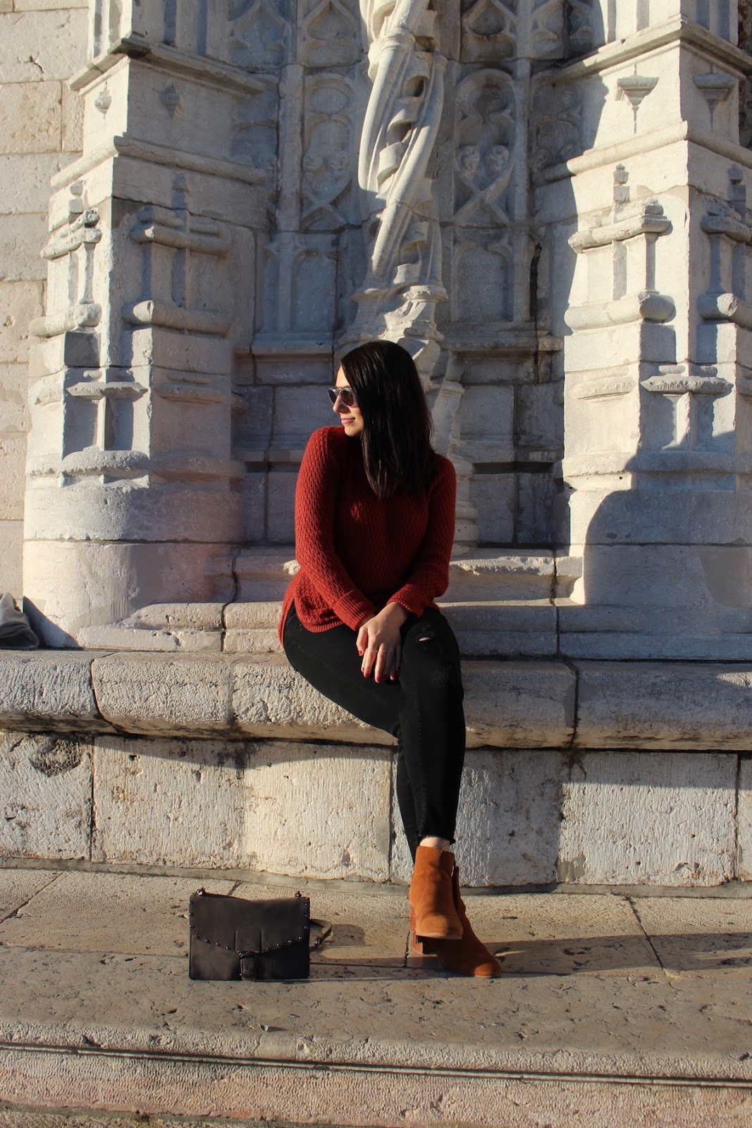 This photo is me in my red sweater, black jeans, sunglasses and heeled booties, sitting on the steps of the Lisbon Cathedral in Lisbon, Portugal.